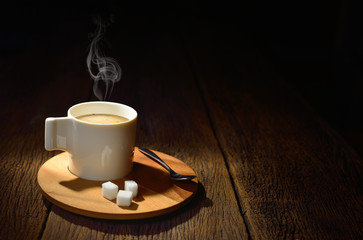 Cup of coffee with smoke and sugar cube on old wooden background