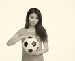 Asian girl taking soccer ball in her hands. Isolated on white.