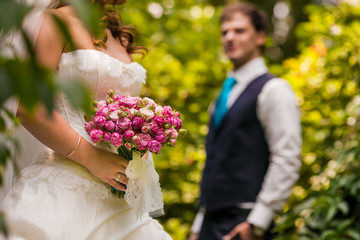 groom looking on the bride holding bridal bouquet close up