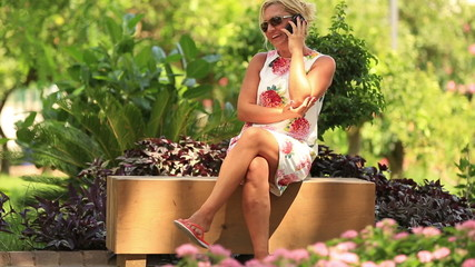 attractive blonde women talking smartphone in park