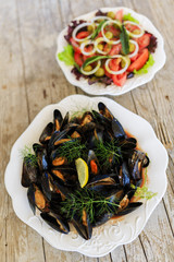 Mussels on plate and mediterranean salad