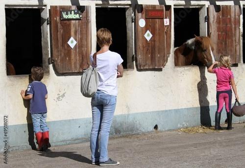 Foto op Plexiglas Paardrijden fillette caressant un cheval à l'écurie