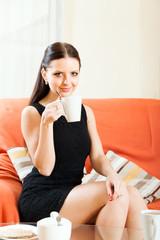 lady in black on  sofa with  mug