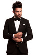 fashion elegant man in tuxedo fixing his sleeve