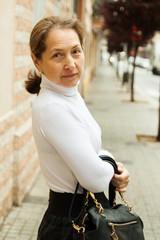 mature woman on  sidewalk