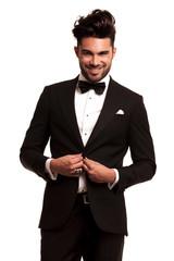 happy young elegant man in tuxedo buttoning his coat