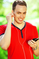 Happy young man in red t-shirt listening to music on phone