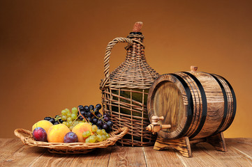 Wicker wine bottle, grapes and wooden barrel