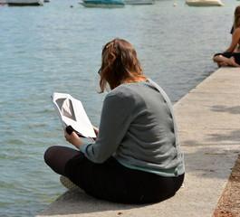femme assise à même le sol feuilletant une revue