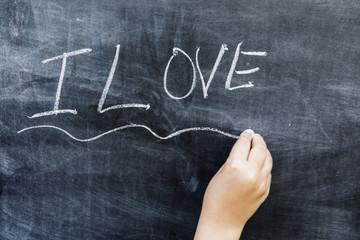 Niño escribiendo I LOVE en una pizarra