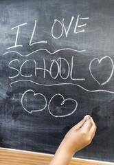 Niño escribiendo I LOVE SCHOOL en una pizarra