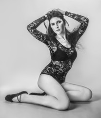 beautiful fashion female sits dressed in a lace bodysuit
