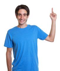 Mann mit schwarzen Haaren zeigt nach oben