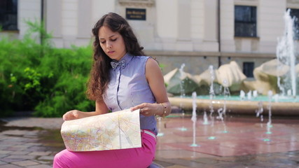 Woman sitting next to the fountain and reading map
