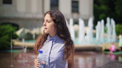 Woman drinking water from a bottle next to the fountain