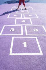 Niño saltando juego de números en el suelo