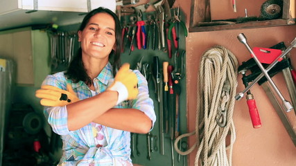Woman putting on gloves and smiling to the camera in the garage