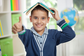 funny schoolboy with a book on head