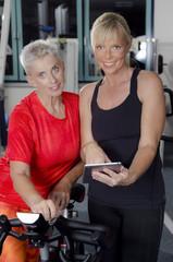 Reife Frauen im Fitness Studio am Spinning Rad besprechen das Tr