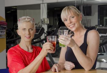 Reife Frauen im Fitness Studio an der Bar beim Entspannungsdrink