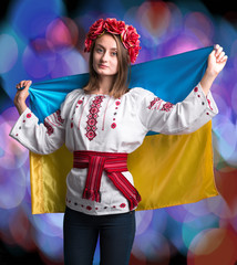Attractive young  girl in national dress with  Ukrainian flag