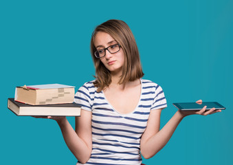 Young girl  holding a book in one hand and a tablet-pc in the ot