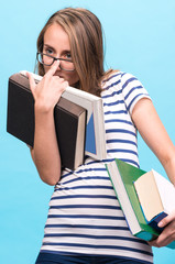 Attractive student girl in glasses with books