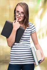 Attractive student girl in eyeglasses with books