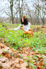 Young woman with flower wreath on her head autumn outdoors