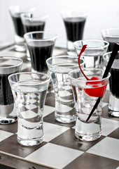 Chess board with shot glasses with red cherry