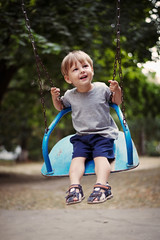 Happy little boy swinging on a swing