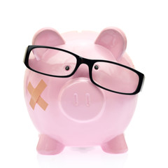 Piggy bank with eyeglasses and bandage