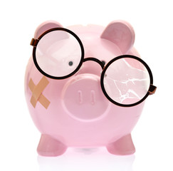 Piggy bank with broken eyeglasses and bandage
