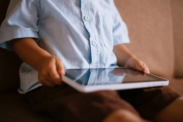Little boy holding a tablet on his lap