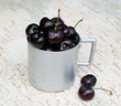 Vintage aluminium mug full of fresh cherries