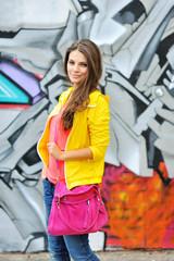 Beautiful stylish fashion woman at graffiti wall in city