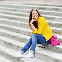 Happy young girl sitting on the stairs and smiling