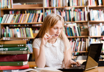 pretty female student using laptop in library