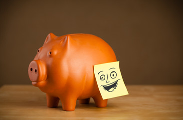 Post-it note with smiley face sticked on a piggy bank