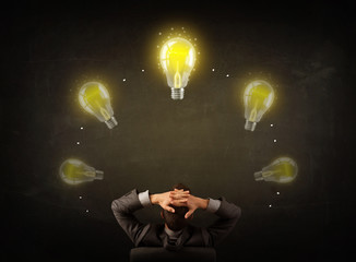 Businessman sitting with lightbulbs over his head