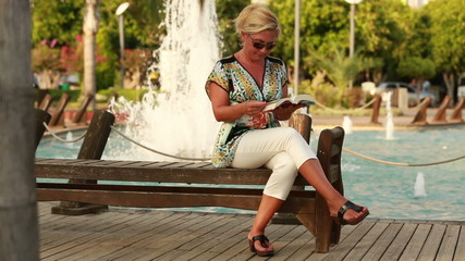 attractive blonde women reading a book in the park