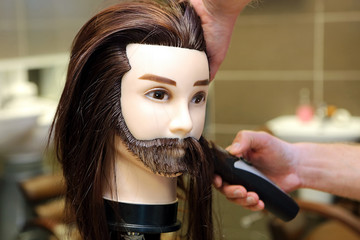 Barber student trimming brown hair using puppet and electric tri