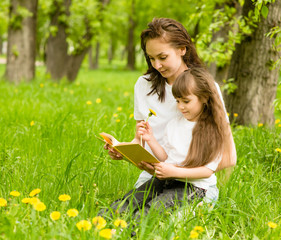 mother with young girl reading book in park