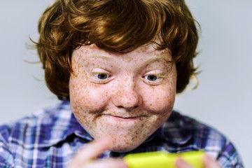 Comic freckled red-haired boy with mobile phone