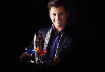 barman with shaker and a glasses on a black background