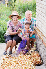 elderly couple and granddaughter with onions