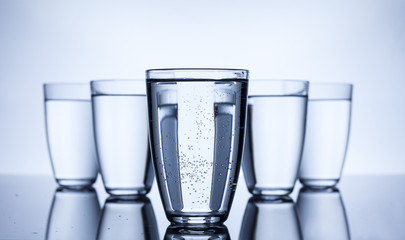 group of five full glasses with water