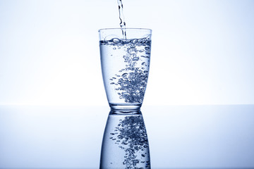 Water flows into the glass and makes bubbles