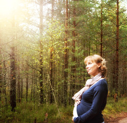 Pregnant woman in forest in morning light