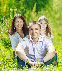 Happy family at picnic on the summer meadow
